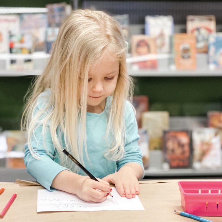 Preschool age girl writing a homemade card - crafts
