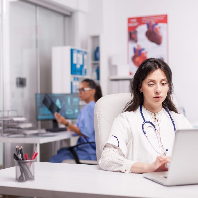 Young therapist using laptop in clinic