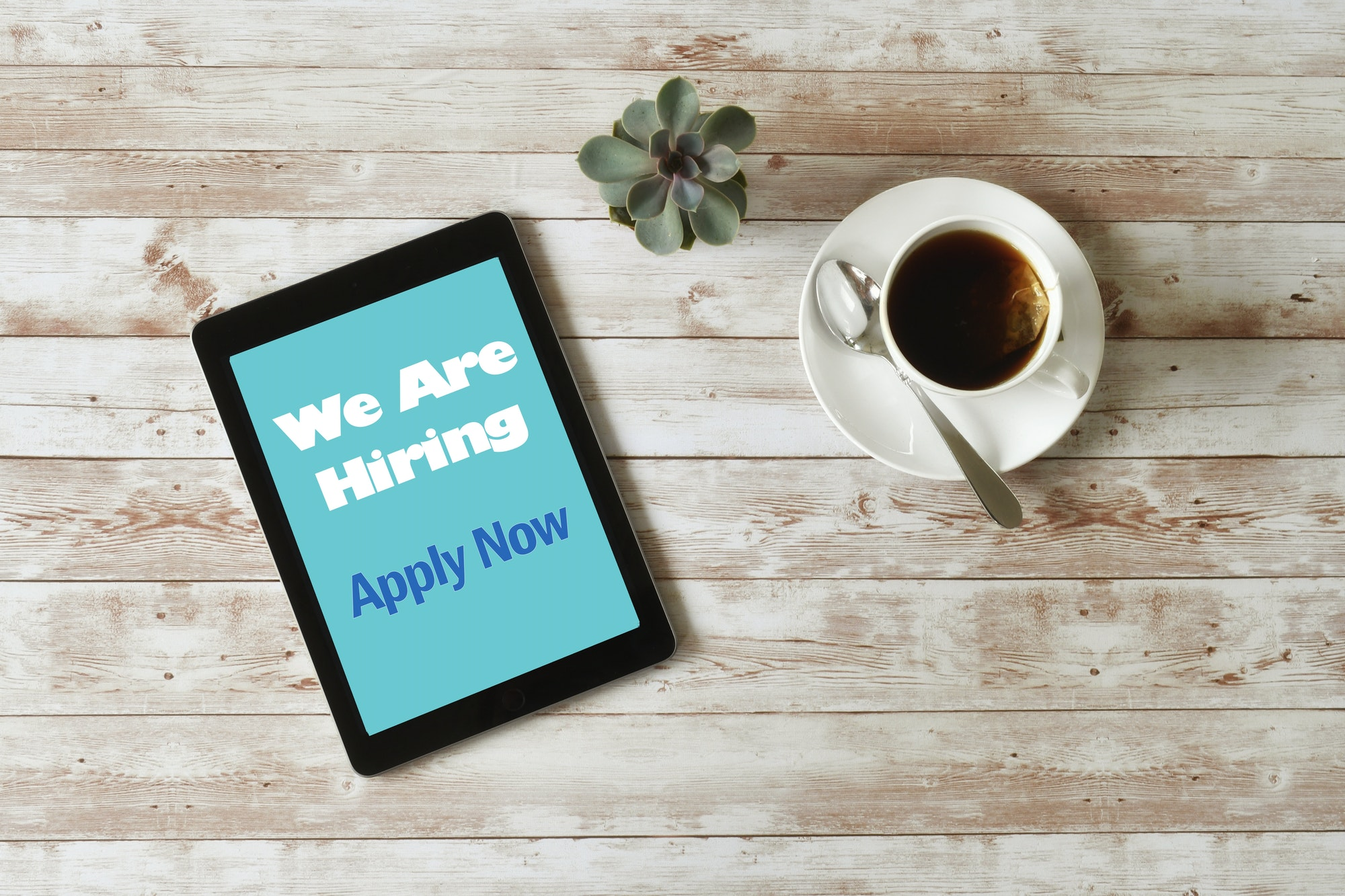 Online Job Search - We are Hiring Apply Now on tablet screen, minimal desk, overhead high angle iPad